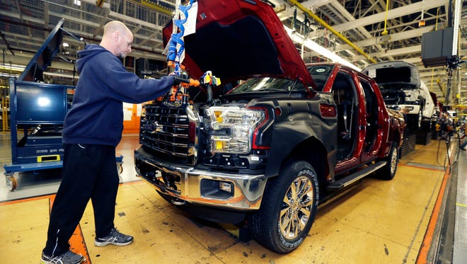 Chris Lucking installs a grill on a new Ford F-150 truck at the Dearborn Truck Plant in Dearborn, Mich.