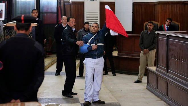 Canadian Al-Jazeera English journalist Mohamed Fahmy holds up an Egyptian flag after a retrial near Tora prison in Cairo, Egypt, on Thursday, Feb. 12, 2015.