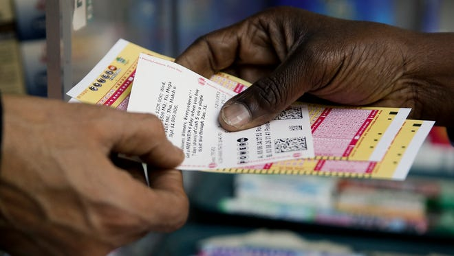 A person purchases Powerball lottery tickets from a newsstand in Philadelphia. Players will have a chance Saturday night at the biggest lottery prize in U.S. history.