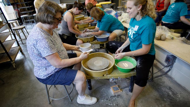 Doris Futoma (left) created a clay piece with the help of Jessica Greene during a demonstration at the 2012 Broad Ripple Art Fair in the Indianapolis Art Center.