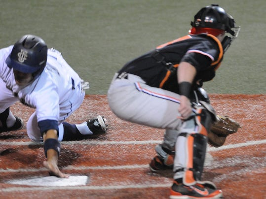 UC Irvine's Chris Rabago gets his hand on the plate as he scores the third run of the inning for the Anteaters in front of Oregon State catcher Logan Ice during an NCAA college baseball regional tournament game in Corvallis, Ore., Saturday, May 31, 2014. (AP Photo/Mark Ylen)