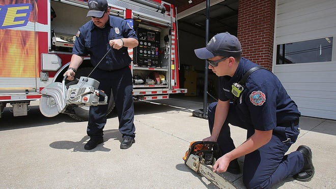 North Lawrence Township Firefighters Ben McCullough (left) and Nathan Cunningham test equipment one one of the trucks.