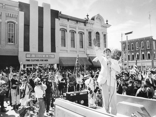 """Louis Beam of Austin, Texas, in the back of truck, leads klansmen and demonstrators in a Nazi salute at the statue of Sam Davis, """"boy hero"""" of the Confederacy, in the Pulaski town square Oct. 7, 1989 as onlookers watch."""