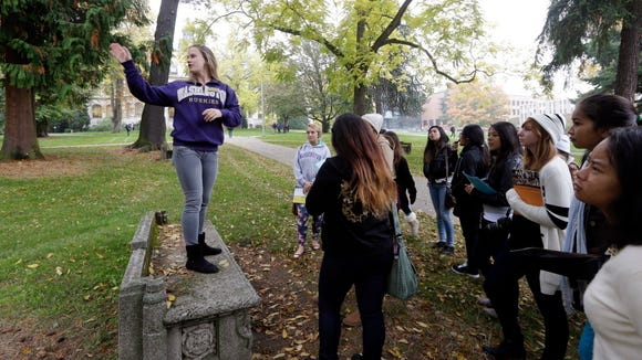 In this photo taken Tuesday, Oct. 15, 2013, University of Washington sophomore Megan Herndon, of Kailua, Hawaii, stands on a bench as she leads high school students on a tour of the campus in Seattle. Despite a downward demographic shift in the number of kids graduating from high school, enrollment is up at three of Washingtonís six public universities this fall. The University of Washington, Western Washington University and Eastern Washington University are all reporting increases in students. UW and Western also have their largest freshman classes ever. Washington State University, Central Washington University and the Evergreen State College are reporting small decreases in fall enrollment. (AP Photo/Elaine Thompson)