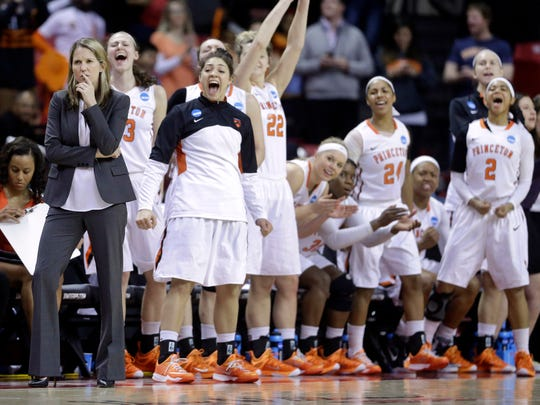 Princeton head coach Courtney Banghart, left, watches as her players celebrate after a play in the first half of an NCAA college basketball game against Green Bay in the first round of the NCAA tournament, Saturday, March 21, 2015, in College Park, Md. Princeton won 80-70. (AP Photo/Patrick Semansky)