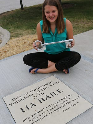 Lia Haile with the key to the city next to her newly inscribed Volunteer Walk of Fame placement.