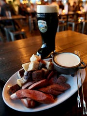 Fondue with smoked German sausages and assorted breads with doppelbock beer at Gustav's Bargarten in Keizer on Friday, Nov. 20, 2015.
