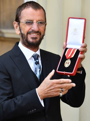 Richard Starkey, better knonwn as Ringo Starr, poses with his medal after being appointed Knight Commander of the Order of the British Empire at an investiture ceremony at Buckingham Palace in London on March 20, 2018.  /
