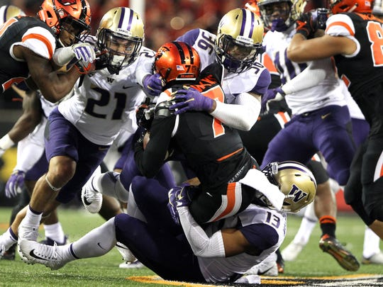 Washington linebacker Azeem Victor (36, center)  was among the Huskies tackling Oregon State receiver Xavier Hawkins during a September game in Corvallis. Victor was expected to be among the conference's best linebackers this year, but he has struggled to earn playing time on a deep Huskies team.
