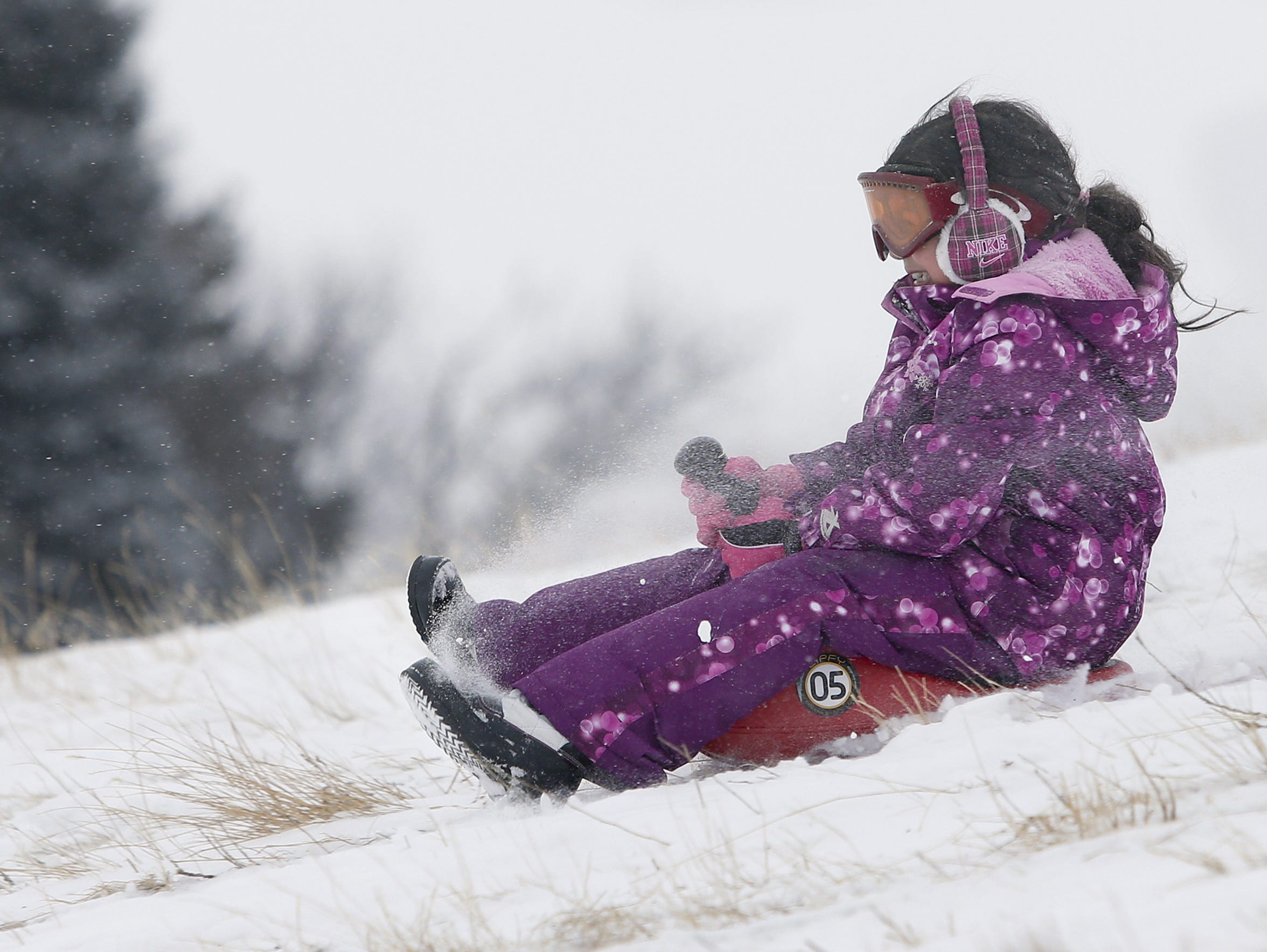 Chloe Montoya holds on tight to her sled as she slides