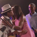 First Lady Michelle Obama (C) greets performer Bruno Mars (L) as President Barack Obama (R) arrives on stage to speak at an Independence Day celebration for military members and their families on the South Lawn of the White House on July 4, 2015 in Washington, DC.