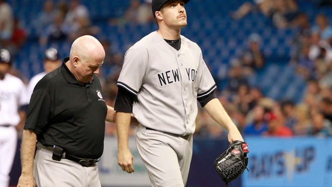 New York Yankees starting pitcher Chase Whitley is taken out of the game by the trainer with an apparent injury during the second inning against the Tampa Bay Rays at Tropicana Field on May 14, 2015.