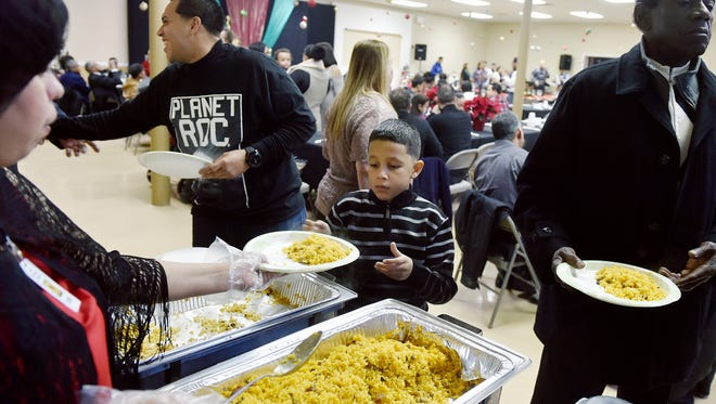 Attendees, including Jahn Baenga, 8, center, go through the buffet line at a Christmas dinner on Saturday, at Iglesia Puerta de Salvación in York. The church will share space in a 26,000 square-foot warehouse with a 501(c)(3) nonprofit called Door of Salvation Community Development, Inc., which plans to provide Spanish-speaking services such as a senior center, a clothes/food pantry, employment services, before- and after-school classes and English as a Second Language classes.