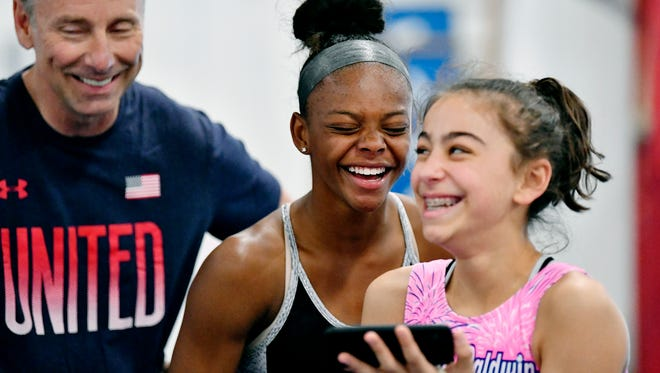Trinity Thomas, center, reacts to a video with coach Tony Fatta and fellow gymnast Addison Fatta, 13, during practice Friday, May 11, 2018, at Prestige Gymnastics in West Hempfield Township, Lancaster County. Thomas, a nationally ranked gymnast, has expanded her athletic repertoire in her senior year to include diving in the winter season and pole vault and track in the spring season.
