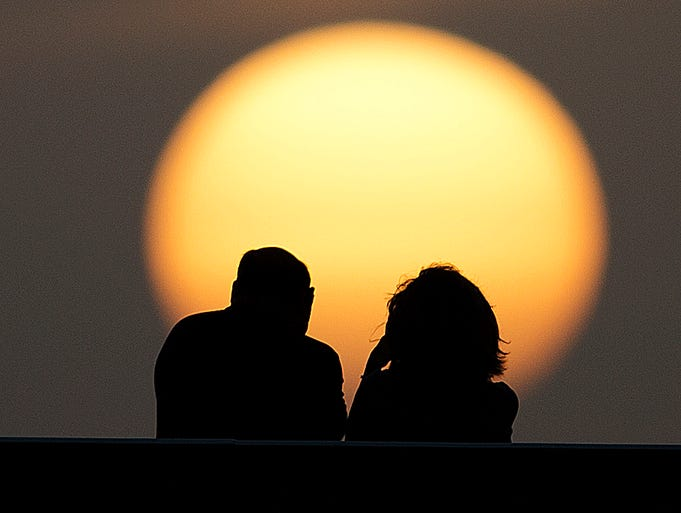 Beachgoers get a look at the setting sun on Fort Myers Beach on Monday 8/18/2014.  A Saharan Air Layer has drifted over the area causing the sun to look more muted.   There are small sand particles from the Sahara Desert in atmosphere.