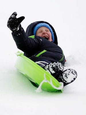 Mitchell Clark, 7, slides down a hill during his first sledding of the season at Reid Middle School in Pittsfield, Mass., on Saturday, Dec. 17, 2016. A winter storm of snow, freezing rain and bone-chilling temperatures hit the nationss mid-section and East Coast on Saturday. (Stephanie Zollshan/The Berkshire Eagle via AP)
