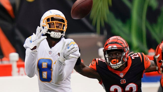 Los Angeles Chargers' Mike Williams (81) makes a catch against Cincinnati Bengals' Darius Phillips (23) during the first half of an NFL football game, Sunday, Sept. 13, 2020, in Cincinnati. (AP Photo/Bryan Woolston)