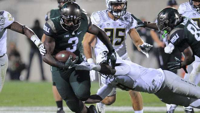 MSU running back LJ Scott picks up some of his 76 yards against Oregon  on Saturday at Spartan Stadium in East Lansing.