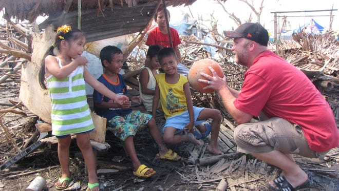 In Cangumbang, a village near Tacloban city on Leyte island, Colorado native Troy Peden, founder of a non-profit that does community projects, organizes volunteers and sponsors children, plays with local children Monday amid the debris of super typhoon Haiyan. Peden, 48, founder of GoAbroad.com, a guide to Ômeaningful travelÕ, is now focused full-time on relief and recovery efforts. ÒWe were built to step up for this,Ó he said of his non-profit Volunteer for the Visayans, founded over two decades ago.