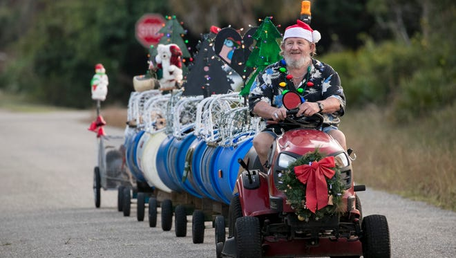 Paul Johnston drives 14 of his 16 dogs in a train he made on Wednesay afternoon. He recently decorated it for Christmas. The dogs love their trips around the neighborhood.