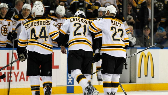 Boston Bruins left wing Loui Eriksson is helped off the ice after being hit by Buffalo Sabres defenseman John Scott.