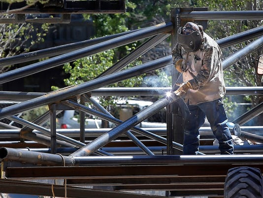 MARK LAMBIEÑEL PASO TIMES  A worker at San Jacinto Plaza welds together the giant 50-foot by 50-foot shade canopy which will shade the center of the new plaza.