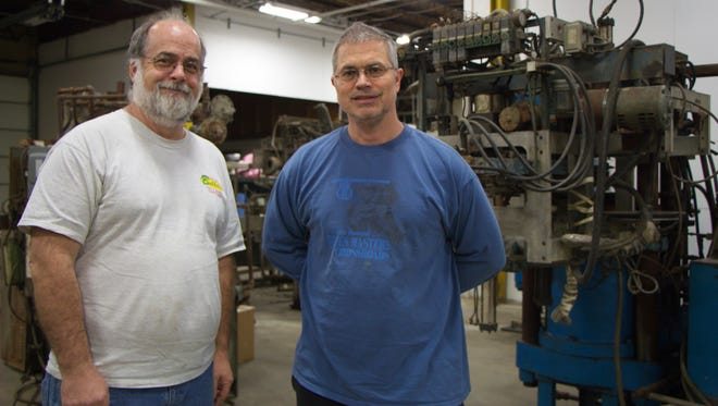 Gary Salstrom, the general manager of Quality Record Pressings, at left, with company owner Chad Kassem. Behind them is one of the vintage record presses the company bought recently.