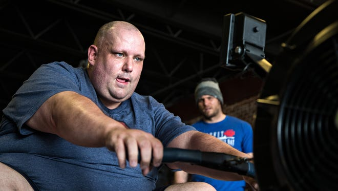 Daniel Finney uses a rowing machine with coach Nate Yoho at CrossFit Merle Hay Monday, March 21, 2016.