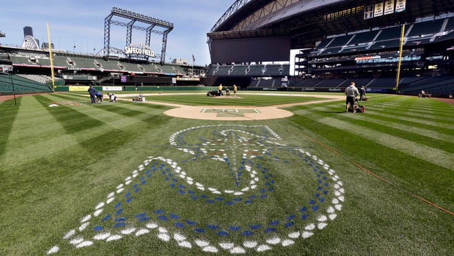 Members of the grounds crew prepare the infield at the Seattle Mariners' ballpark, Wednesday, April 6, 2016, in Seattle. The team opens the home portion of their season against the Oakland Athletics on Friday.