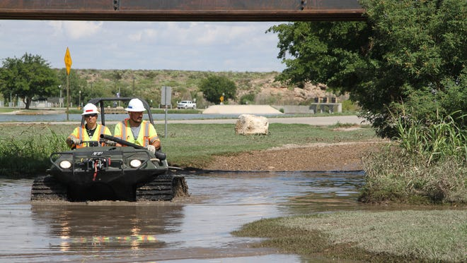 Eddy County Vector Control workers Joey Lawson (left) and Johnny Munoz used the Argo all-terrain vehicle to spray in high-level water puddles after the flash flood over the weekend.