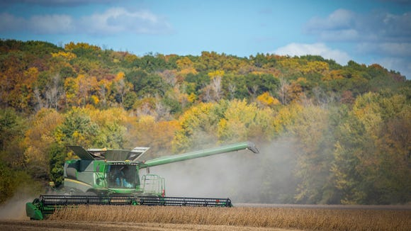 Howard Goodhue combines soybeans near Carlisle, Iowa, Tuesday, Oct 18, 2016. An Iowa State University report shows Iowa farmland values have dropped 5.9 percent, due to the pullback in corn and soybean prices.