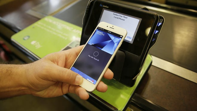 An Apple executive demonstrates the Apple Pay mobile payment system.