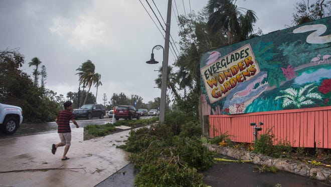 A child runs past the iconic Everglades Wonder Gardens sign, damaged by Hurricane Irma, in downtown Bonita Springs on Monday, Sept. 11, 2017.