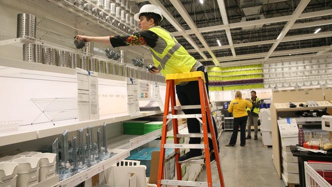 Hannah Tews, a visual merchandiser, sets up products in the market hall at the new Ikea store at I-94 and Drexel in Oak Creek. The store opens May 16.