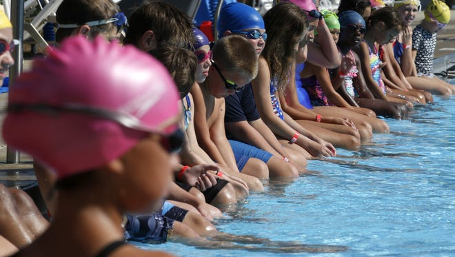 Children line the edges of the pool at the Trousdell Aquatics Center during their World's Largest Swimming Lesson in 2016.