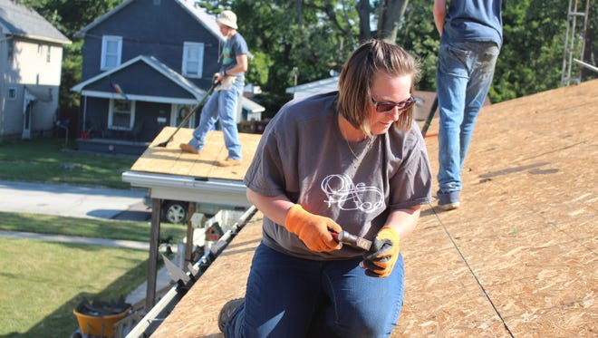 Amber Mead, a member of the Trinity Baptist Church in Marion, helps replace the roof on a home on Wood Street as part of Mission Serve, a Christian organization that arranges mission trips across the U.S. and abroad.