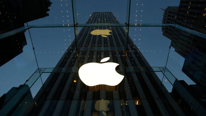 The Apple logo is illuminated at the entrance to the Fifth Avenue Apple store in New York.