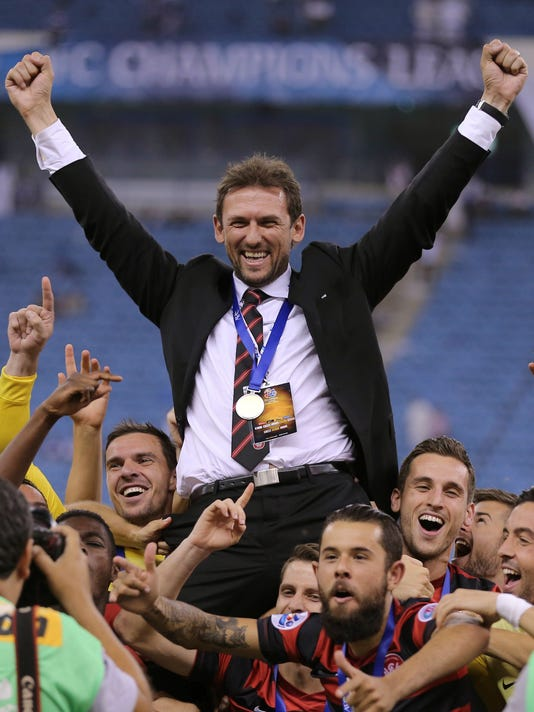 Australia's Western Sydney Wanderers players hold up their head coach Tony Popovic as they celebrate winning the Asian Champions League Final second leg soccer match with a 0-0 draw against Saudi Arabia's Al Hilal at King Fahd stadium in Riyadh, Saudi Arabia, Saturday, Nov. 1, 2014. (AP Photo)
