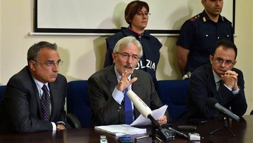 Italian prosecutor Giovanni Salvi, center, is flanked by Catania Police chief Marcello Cardona, left, and deputy prosecutor Andrea Bonomo, as he speaks during a press conference in Catania, Sicily, Southern Italy, Tuesday, May 19, 2015. Giovanni Salvi says authorities have dropped a possible charge of illegal detention against two alleged smugglers being held in connection with a shipwreck believed to have killed more than 800 migrants. Prosecutor Giovanni Salvi told reporters Tuesday that investigators now believe that the doors were closed to secure the boat and not to detain hundreds of migrants on two lower decks as prisoners. Many of the victims were believed to have perished closed inside the overcrowded fishermen's boat when it sank near the Libyan coast on April 18. (AP Photo/Carmelo Imbesi)