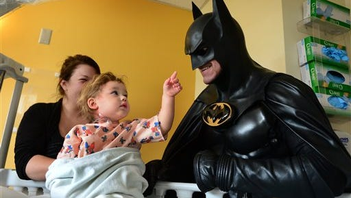 In this Aug. 15, 2014 photo, Leonard Robinson, dressed as Batman, visits Mattie Dillon on the pediatrics floor of Charleston Area Medical Center Women and Children's Hospital in Charleston, W.Va. The Maryland man who delighted thousands of children by impersonating Batman at hospitals and charity events died when he was hit by a car while standing in the fast lane of Interstate 70, checking the engine of his custom-made Batmobile, police said Monday, Aug. 17, 2015.