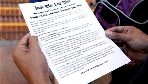 In this Monday, Oct. 19, 2015 photo, Jerome Palma holds a flyer given to him by Alexander Rowson outside Everett Middle School in San Francisco. A student election at a mostly black and Hispanic middle school turned into a fierce debate about the democratic process when the school's principal delayed announcing the election results over concerns they did not reflect the school's diverse student body. (Connor Radnovich/San Francisco Chronicle via AP) MANDATORY CREDIT FOR PHOTOGRAPHER AND SF CHRONICLE; NO SALES; MAGS OUT; TV OUT