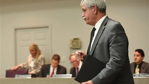 """Hamilton County Schools Superintendent Rick Smith enters a school board meeting room before a short public meeting in Chattanooga on Wednesday. Tennessee's Ooltewah High School has called off the rest of its basketball season after three of its players were arrested on charges of raping a teammate in an apparent hazing incident. Smith said he was taking this """"very unusual step"""" with the high school """"so that the criminal justice system can work the way we expect."""""""