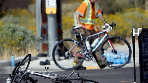 Emergency personnel wheel off a bike past another badly damaged bicycle in the aftermath of a collision involving a vehicle and several bicyclists Thursday, March 3, 2016 northwest of Tucson, Ariz. The Pima County Sheriff's Department says two bicyclists were killed after an impaired driver struck them in northwest Tucson.