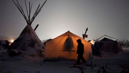 In this Tuesday, Nov. 29, 2016 photo, a light inside a tent glows as a person walks by at the Oceti Sakowin camp where people have gathered to protest the Dakota Access oil pipeline in Cannon Ball, N.D. The number of inhabitants has ranged from several hundred to several thousand. It has been called the largest gathering of Native American tribes in a century.