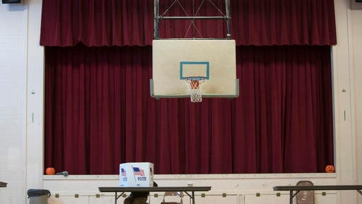 A voter fills out a ballot in the gymnasium at the St. Mary's Academy building on Tuesday, Nov. 8, 2016, in Hudson, N.Y.