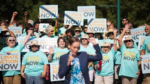 Clean air advocates cheer as Mary Anne Hitt, director of the Sierra Club's Beyond Coal Campaign, speaks at a rally outside an Environmental Protection Agency hearing, Tuesday, July 29, 2014, in Atlanta. Utility and coal companies are expected to argue Tuesday against proposals from the Obama administration that would force a 30 percent cut in carbon dioxide emissions by the year 2030 from 2005 levels. The EPA is holding three public hearings on the proposal in Atlanta, Denver and Washington.