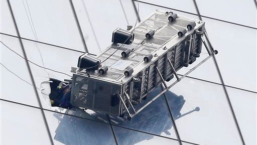 A firefighter reaches through a cut-out window into a dangling work basket to rescue two workers from the 60th floor of 1 World Trade Center in New York, Wednesday.