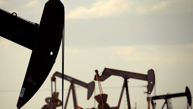 In this April 24, 2015 photo, pumpjacks work in a field near Lovington, N.M. As New Mexico's elected leaders wrangle over raising taxes to plug a budget shortfall, major energy companies have quietly spent more than $13 billion in recent months to buy up assets in the state's oil and gas hot spots. Analysts say the new wave of investment bodes well for the industry being able to generate much-needed revenues for the struggling state over the long haul.