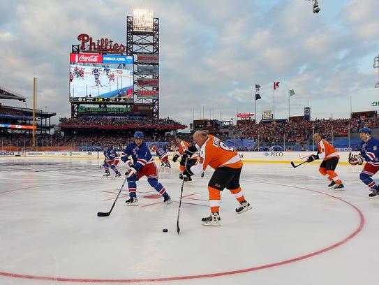 Bob Kelly #9 of the Philadelphia Flyers plays the puck