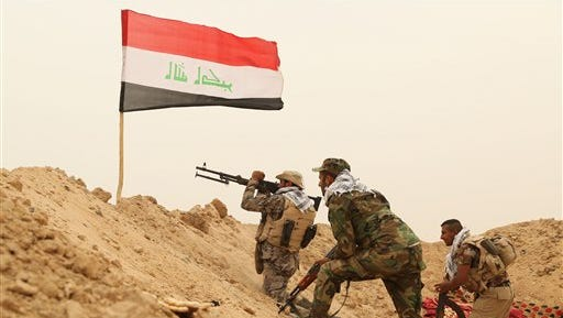 Fighters from the Badr Brigades Shiite militia clash with Islamic State militant group at the front line, on the outskirts of Fallujah, Anbar province, Iraq, Monday, June 1, 2015. Three Islamic State suicide bombers targeted a police base in the Tharthar area north of Ramadi, some 30 miles (48 kilometers) west of Fallujah, with explosives-laden Humvees on Monday, killing at least 41 police and Shiite militiamen, officials said. (AP Photo/Hadi Mizban)